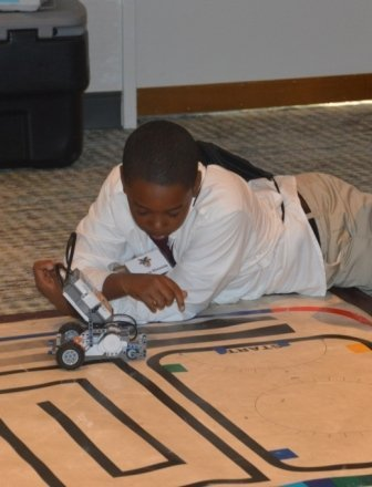 Student on floor with robotic vehicle