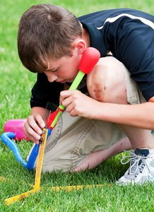 Student building a rocket in the grass