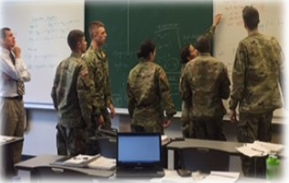 Cadets solving problems on whiteboard with professor