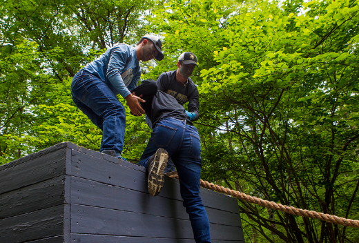Teens from the 2018 Summer Leaders Experience help others through obstacles.>From Media Library